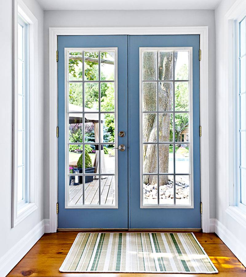 sky blue front door with window details from top to bottom with striped carpet in front of it