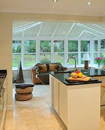 new white conservatory installation with view from the kitchen
