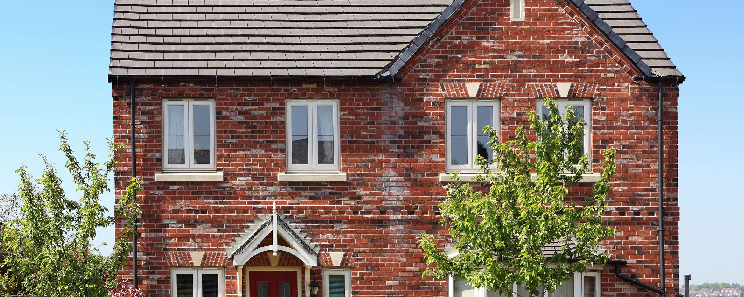 Red brick house with new white window installations