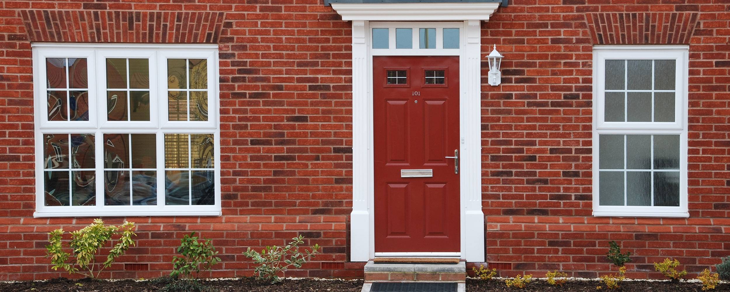 Red front door on front of modern red brick house