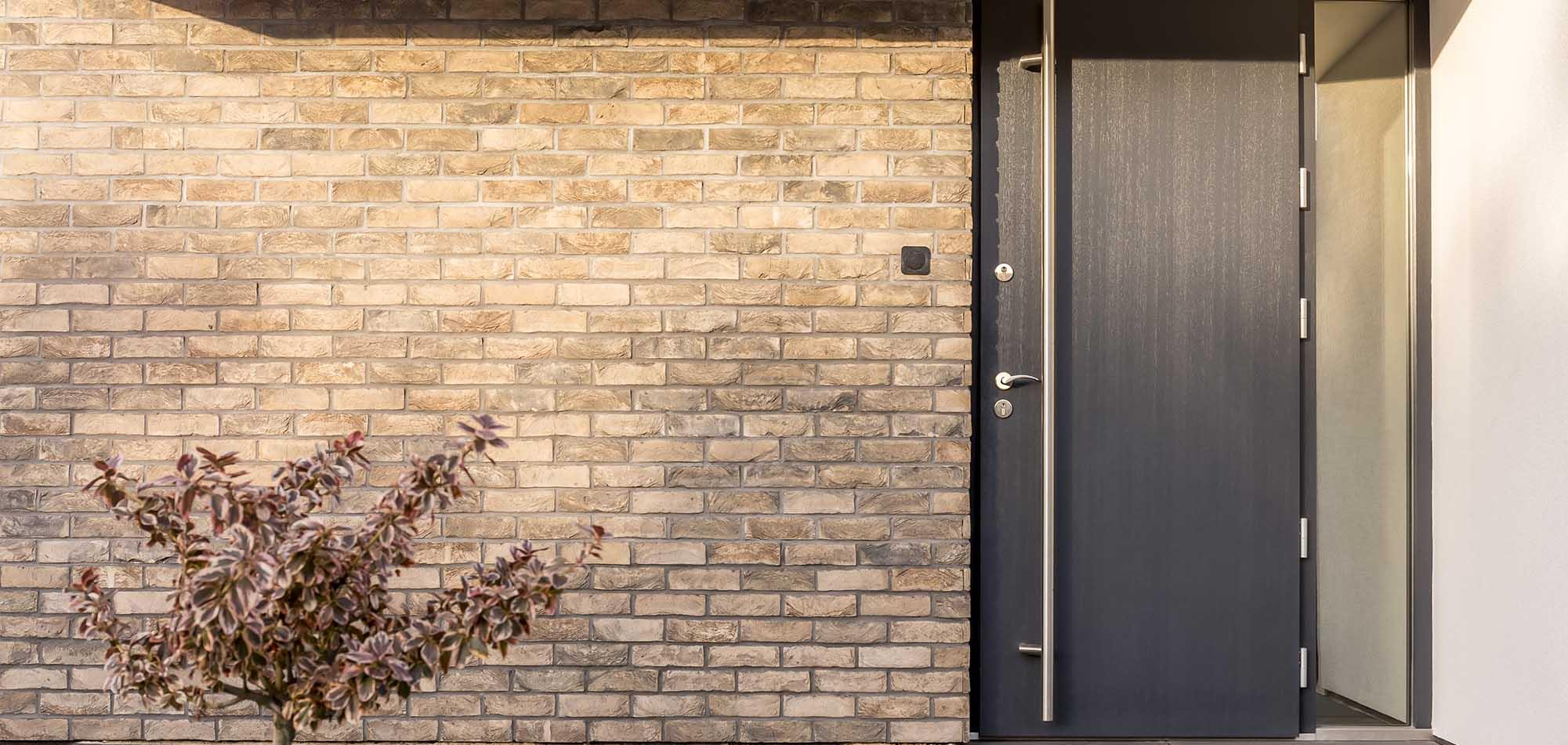 Dark composite door on the front of brick house